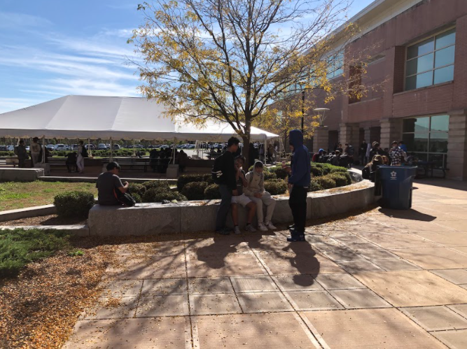 Students forced to find seating scattered across the courtyard due to overcrowding under the picnic table.